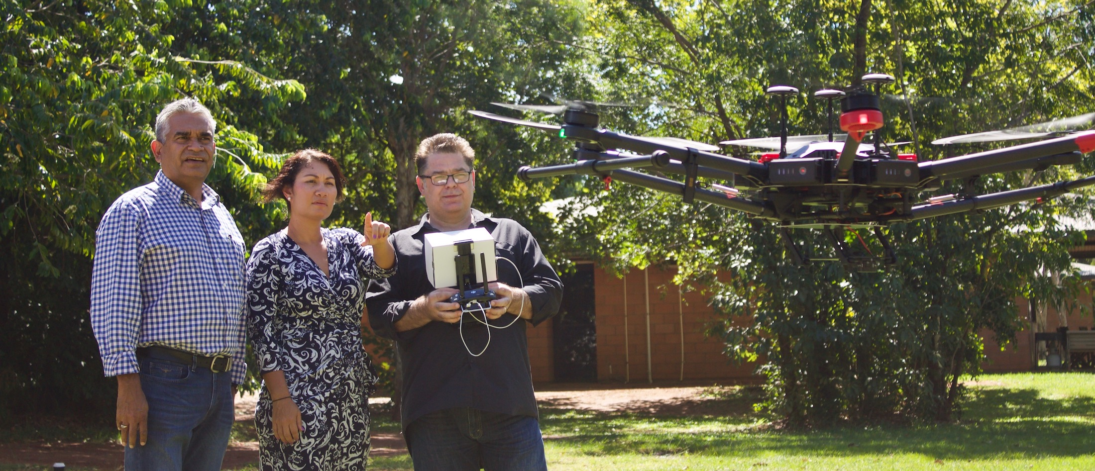 IMG_Acting CEO Ms Anstess watching Mr Coyne take the new drones for the first of many flights at Batchelor Institute, with Dr Stephen Hagan Senior Director Alliance Management copy